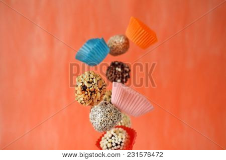 Flying Sweets With Different Sprinkles And Paper Cups On Colourful Orange Background