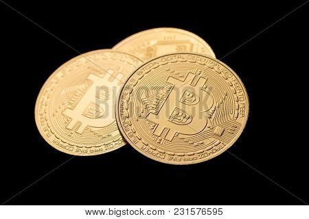 Three Golden Bitcoin Coins On Black Background