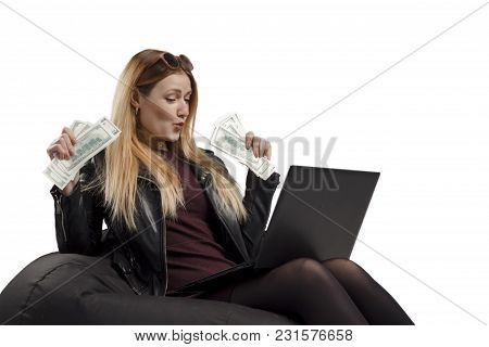 Young Woman Earns Crypto Currency, Girl Sits On A Soft Chair With A Laptop And Dollars In Hands, Bit