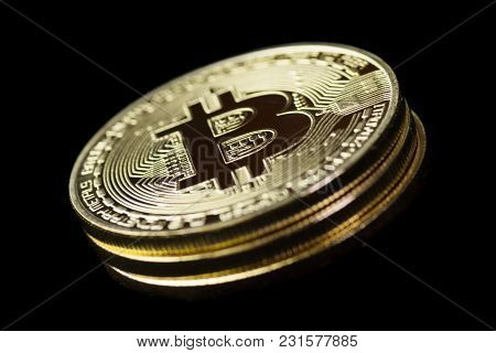 Stack Of Three Golden Bitcoins On Black Background