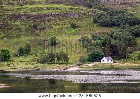 Stromeferry, Scotland - June 10, 2012: Small White Cottage Built On Shoreline Of Loch Carron. Silver