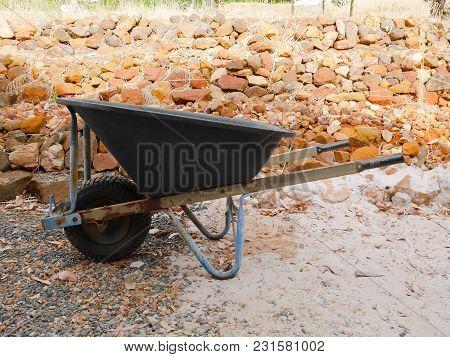 Wheelbarrow On Backyard In Rural Area. Construction Tool.