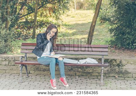 Young Beautiful School Or College Girl With Glasses Sitting On The Bench In The Park Reading The Boo