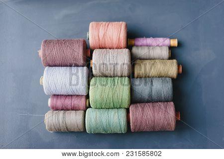 Multicolored Vintage Thread Spools On A Blue Background