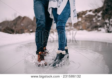 Male And Female Legs In Boots Stand In Puddle Of Melted Water With Flying Apart Water Splashes. Clos