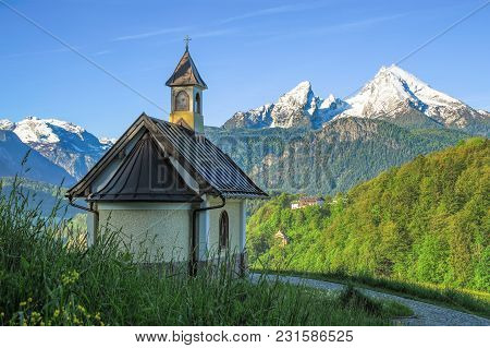 Spring Landscape With Small Chapel And Snow-covered Watzmann Mountain In Bavarian National Park Berc
