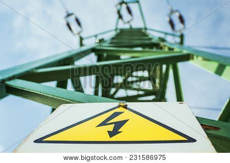 Green Electric Mast (power Tower)  With Yellow Warning And Caution Sign (high Voltage) And Blue Sky