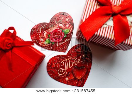 Red Postcards On Valentine`s Day Lie Among The Gift Boxes Of Red Color.