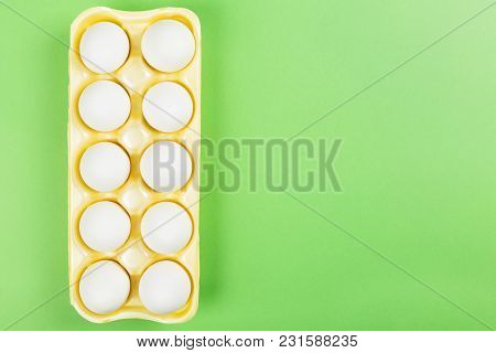 White Eggs In Yellow Container For Eggs On Green Background. Top View, Copy Space. Food Background