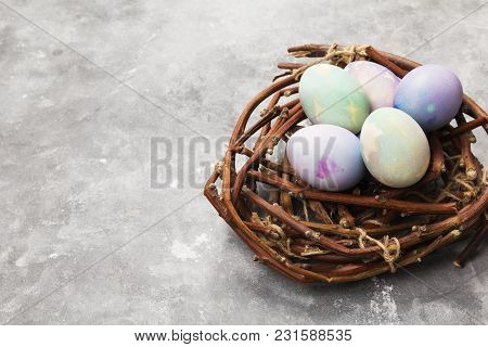 Multicolored Eggs For Easter In Nest On Gray Background. Copy Space. Food Background