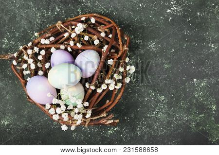 Multicolored Eggs For Easter In Nest With Flowers On Green Background. Top View, Copy Space. Food Ba