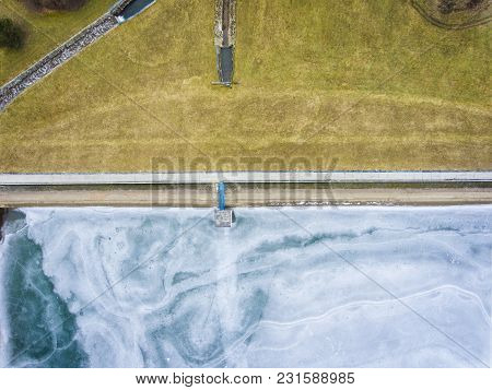 Aerial Drone Image Of Frozen Lake And Dam With Snow Next To The Meadow With Grass. Ice From The Dron