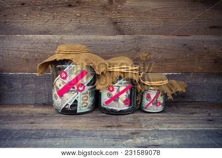 Three Glass Jars With Dollars, Percent From Bank Deposits