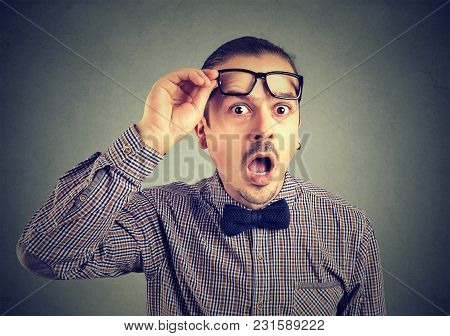 Young Handsome Man In Formal Outfit Lifting Up Glasses Looking At Camera In Great Astonishment.