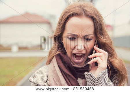 Young Brunette In Coat Talking On A Phone Outside And Screaming In Stress Having Bad Breakup.