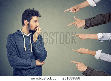Anxious Man Judged By Different People. Concept Of Accusation Of Guilty Guy. Negative Emotions Face
