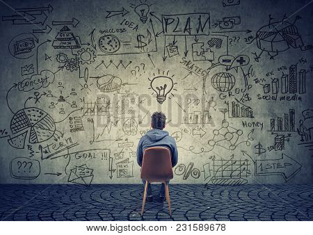Back View Of A Man Sitting In Front Of Wall With Strategy And Creating Business Plan.