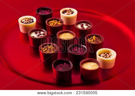 Assortment Of Luxury White And Dark Chocolate Candies Variety On Red Plate
