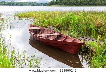 Old Fishing Wooden Boat At The Lake In Sunny Summer Day