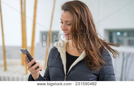 Smiling, Brown-haired woman in video conference with the mobile. talking on the street with your partner through the use of new technologies