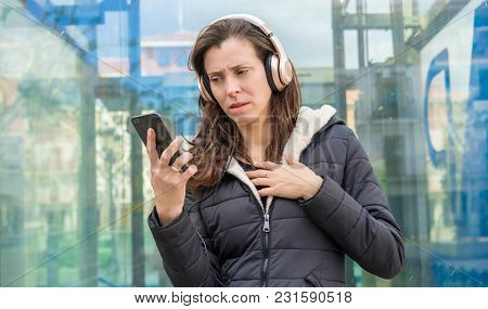 jealousy and suspicion in the cell phone, couple problems, adult woman looking at suspicious messages on the phone while on the street listening to music with headphones