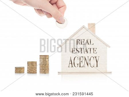 Wooden House Model With Coins Next To It And Hand Holding The Coin With Conceptual Text.real Estate