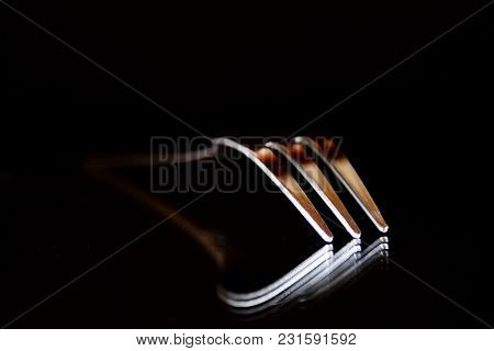 Shiny Fork With Three Spikes Reflecting  On A Mirror