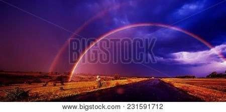 Blurred, Rainbow In The Field Rain And Dark Clouds. Spring Season, Evening. Panoramic And Web Banner