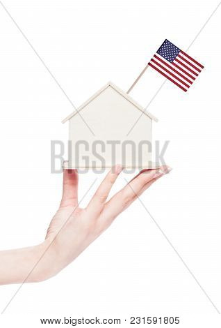 Female Hand Holding Wooden House Model With United States Of America Flag On Top.