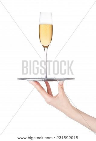 Hand Holds Tray With Glass Of Yellow Champagne With Bubbles On White Background With Reflection