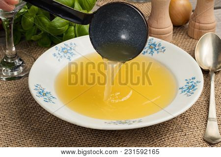 Pouring Chicken Bone Broth Into A Soup Plate With An Old Ladle