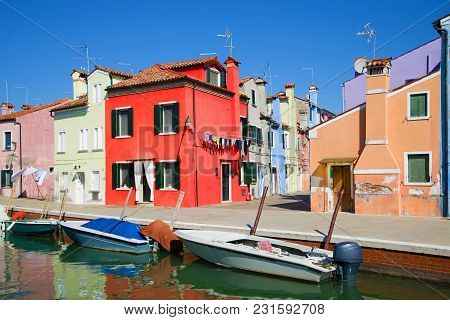 Red House On The Embankment Of The City Channel. Sunny Day On The Burano Island, Venice