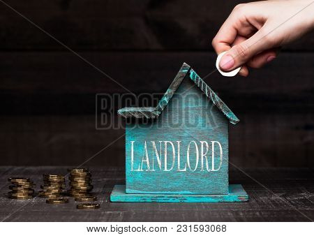 Wooden House Model With Coins Next To It And Hand Holding The Coin With Conceptual Text. Landlord