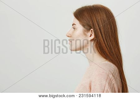 Profile Photo Of Attractive Redhead Woman With Cute Freckles Looking Aside And Standing Over Gray Ba