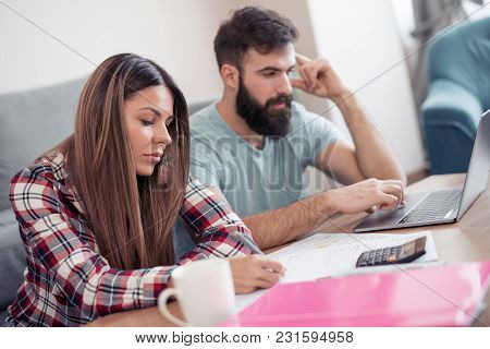 Worried Couple Checking Their Bills At Home.