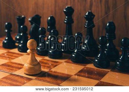 Old Chess - Small Pawn Standing In Front Of Set Of Black Chess Pieces.
