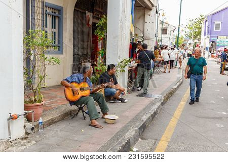 George Town, Penang, Malaysia - November 26, 2017: A Man Plays A Guitar On The Street Of Georgetown