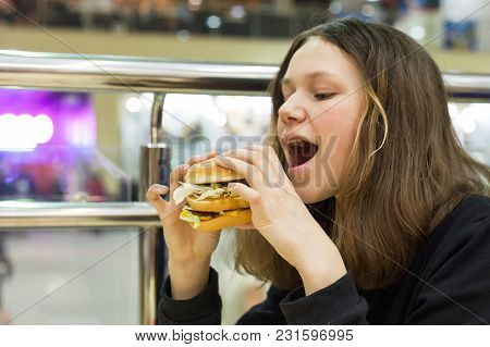 Teenage Girl Eating Burger, Background Shopping Mall Entertainment Center.