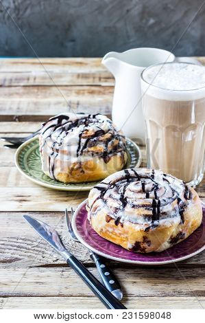 Cinnamon Rolls Or Cinnabons With Cream Sauce, Sweet Traditional Dessert Buns Pastry Food. Selective