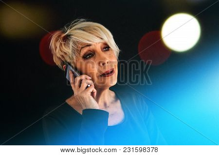 A Successful Positive Elderly Female Consultant Is Negotiating A Cell Phone. Communication Between P