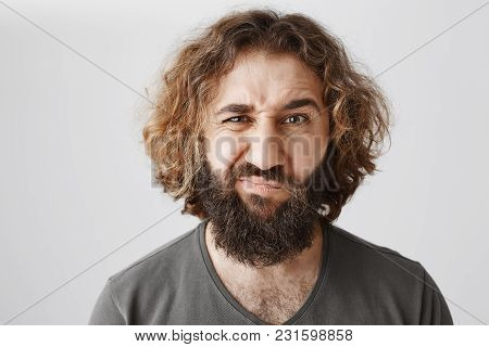 Doubt That Idea Is Good. Indoor Shot Of Displeased And Uncertain Adult Eastern Guy With Beard And Cu