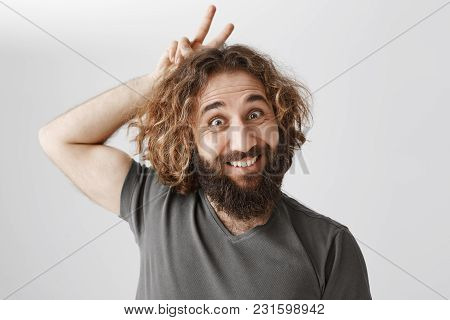 May I Be Your Easter Bunny. Portrait Of Funny Playful Curly-haired Male With Beard Holding V Sign Or