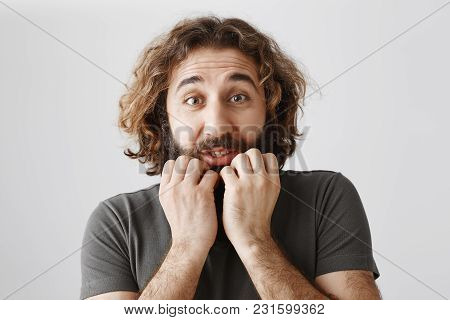 Man Trembling From Fear. Indoor Shot Of Scared Adult Bearded Guy With Curly Hair Holding Hands On Ja