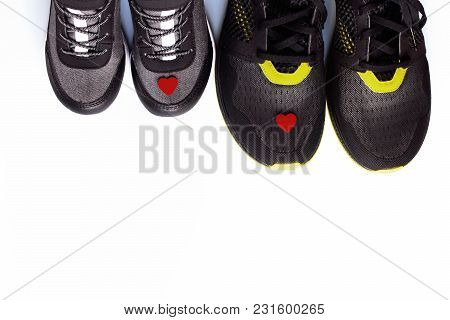 Grey Kid Sneakers With Little Red Heart And Pair Of Black Adult Sneakers On White Background With Sp