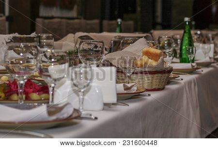Served Table In Restaurant, Glasses, Dishes With Cheese And Bread For A Holiday