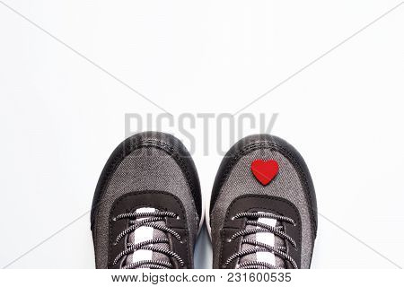 Pair Of Grey Cute Kid Sneakers With Little Red Heart On White Background With Space For Text As Gree