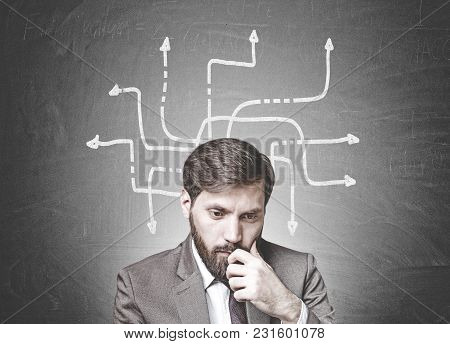 Young Businessman With Dark Hair And A Beard Wearing A Suit Is Thinking. Concept Of Doubt And Choice