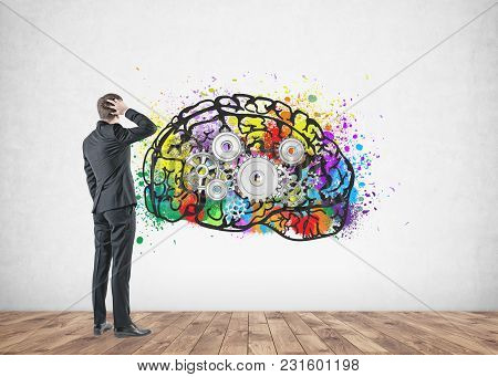 Rear View Of A Confused Businessman Scratching His Head And Thinking. A Concrete Wall Background Wit
