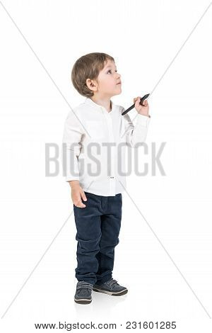 Cute Little Boy In A White Shirt And Dark Jeans Holding A Marker And Looking Upwards. An Isolated Po