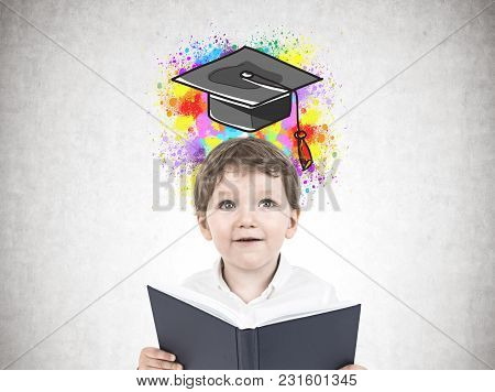 Portrait Of A Cute Little Boy In A White Shirt Holding An Open Book And Looking Upwards. A Concrete